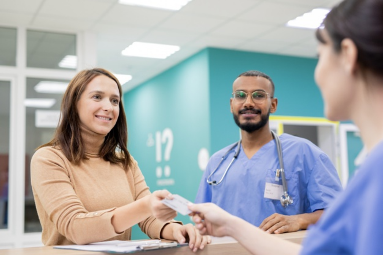 woman-paying-via-credit-card-at-hospital-reception